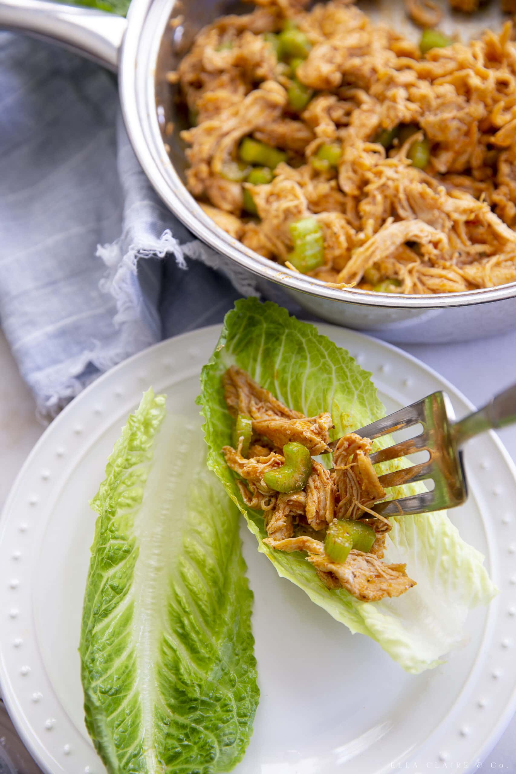 putting filling for buffalo chicken lettuce wraps into the lettuce slhells