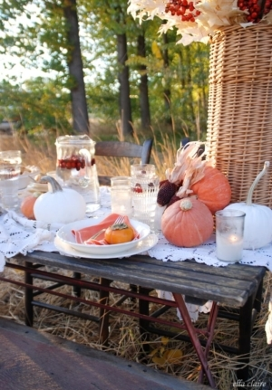 Lovely Autumn tablescape with pumpkins, gourds, berries, persimmons, candlelight, and plenty of rustic vintage charm!