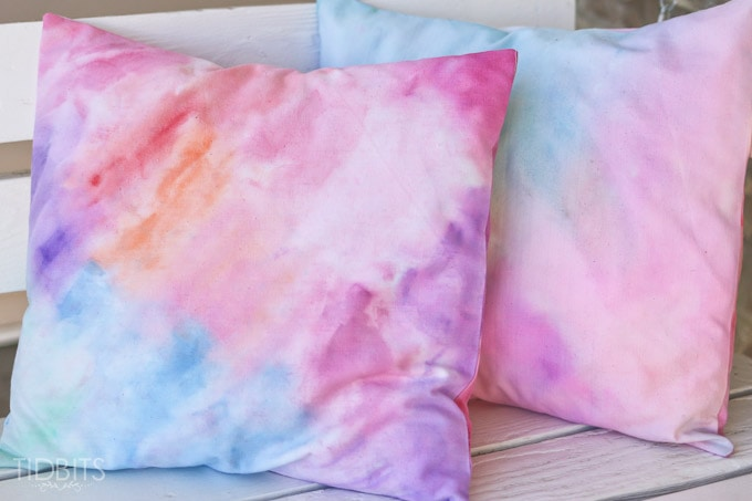 A stack of pillows showing how the DIY watercolor technique looks on fabric.