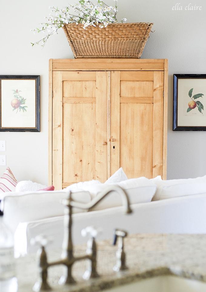 antique cabinet, cream sofas | Ella Claire Summer Home Tour