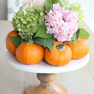 A simple, elegant DIY Fall centerpiece using pumpkins and hydrangeas adds a fun, rustic feeling to your Autumn table!