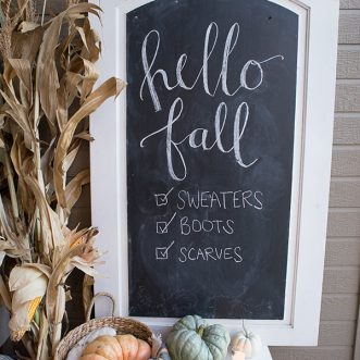 Add a Fall chalkboard, baskets, corn stalks, pumpkins and gourds to create a simple, rustic farmhouse style Autumn porch. #ideas #decorating #frontdoors #cheap #modern #whitepumpkins #falldecorating #porch