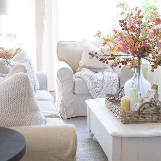 Add warmth and coziness to a family room with layers of cozy throws and pillows with accents of classic Fall colors- burnt orange, cream, reds. #couch #coffeetable #fallcolors #autumn #falldecorating