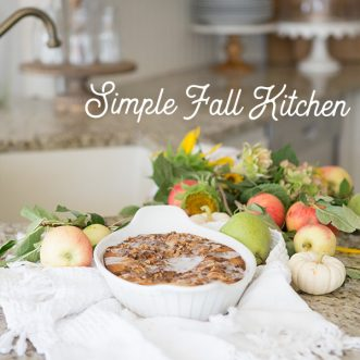 A warm and cozy Fall farmhouse kitchen with white cabinets, vintage accents, breadboards, yummy cake, bread and all the comforts of home. #neutral #warmcolors #jars #falldecorating #autumn #ideas #hometours