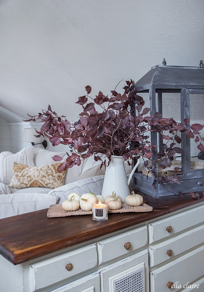 Farmhouse Fall Family Room with Warm golds, plum branches, white pumpkins and candle light.