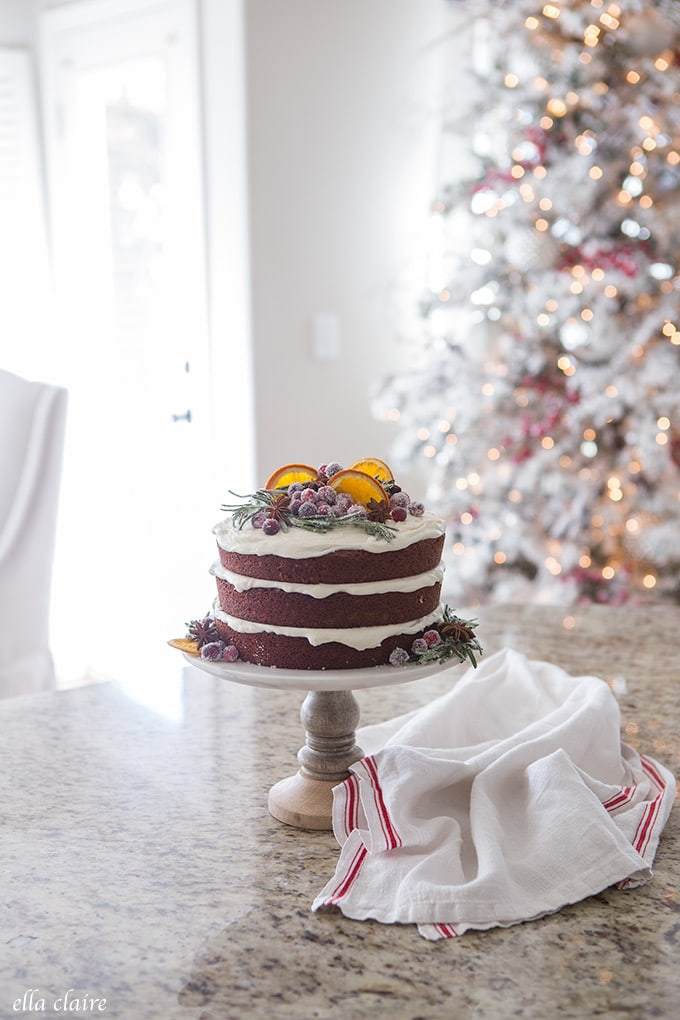 Gingerbread cake with dried oranges, sugared cranberries, star anise and sugared rosemary in a sweet Christmas kitchen