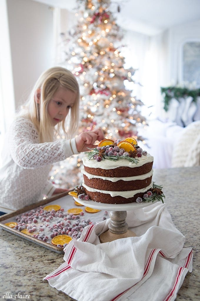 Decorating a gingerbread cake with dried oranges, sugared cranberries, star anise and sugared rosemary.