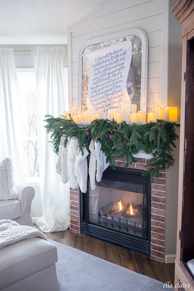 A cozy and inviting Christmas Family room- mantel garland with red bells and mismatched cream stockings