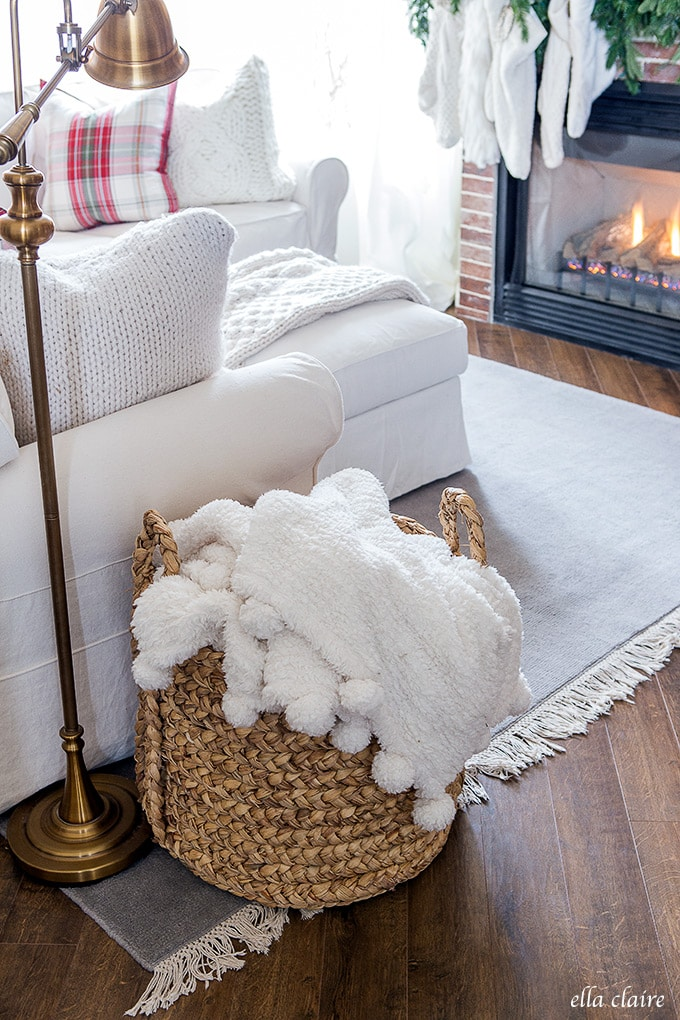 A cozy and inviting Christmas Family room- an oversized basket holds extra blankets for those chilly winter nights