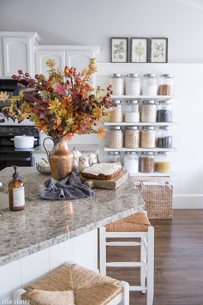 Jar shelved contain pantry staples in this timeless Fall kitchen accented with warm colors, copper, and vintage decor pieces.