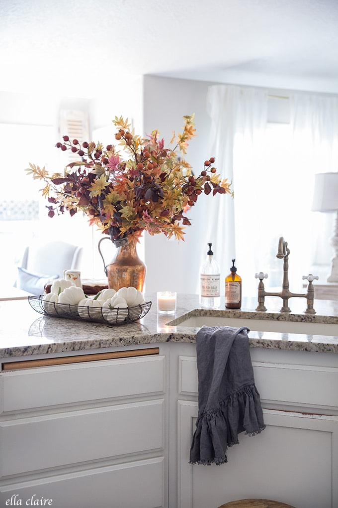 A mixture of faux and real fall branches, leaves, and berries add timeless color and warmth to classic kitchen.