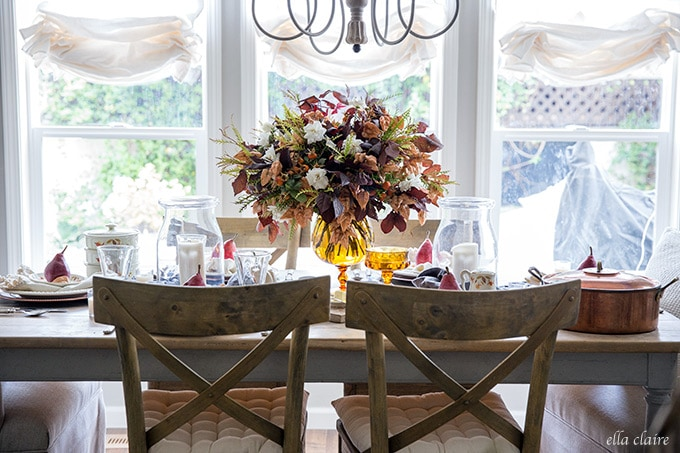 A Fall tablescape using foraged leaves and flowers, amber glass, and vintage dishes