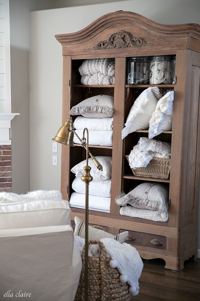 Warm and Cozy Fall Family Room- extra linen storage in a styled open antique armoire