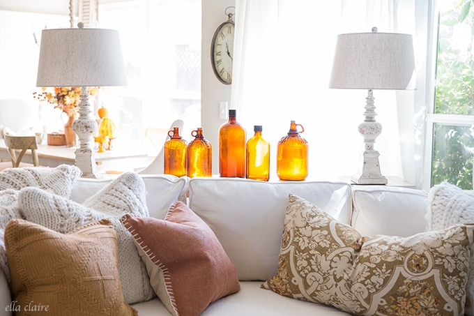 Vintage amber glass bottles are a beautiful decoration for fall in this cozy family room.