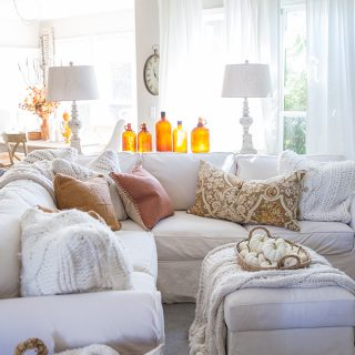Vintage amber glass bottles are a beautiful decoration for fall in this cozy family room decorated with traditional warm autumn colors