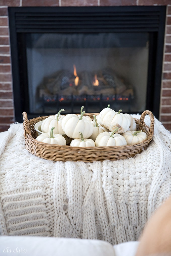 white pumpkins gathered in a basket by the fire make for a simple warm and cozy fall decoration