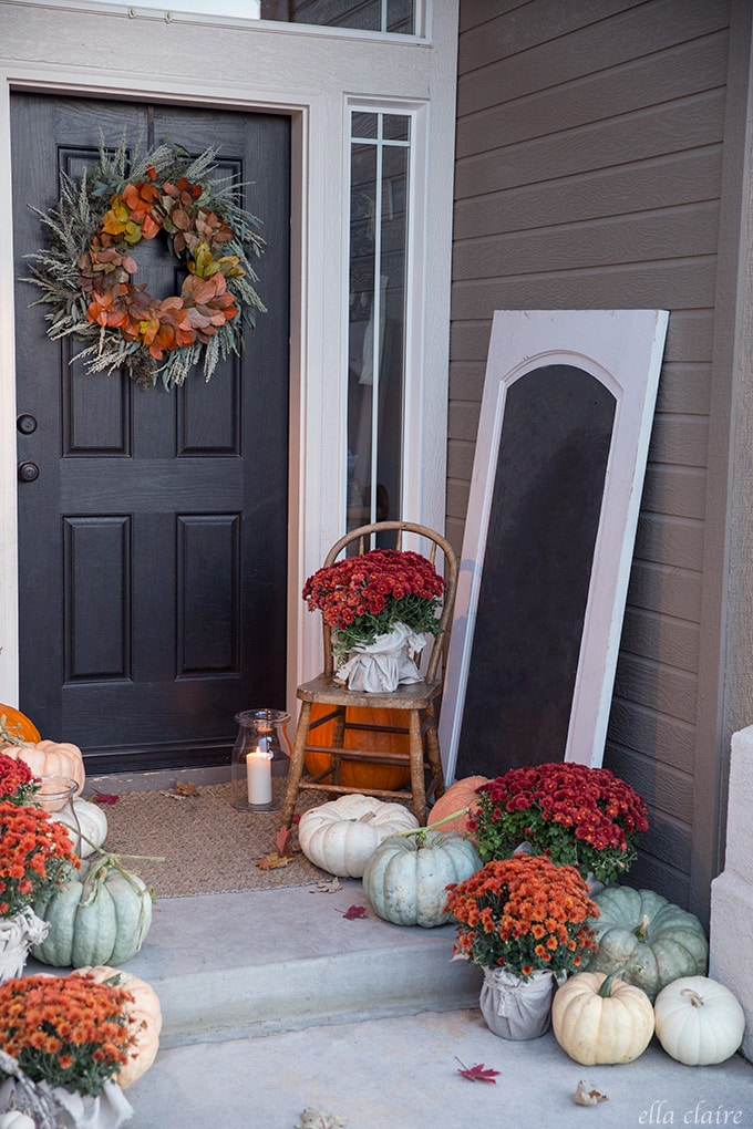 A cozy porch dressed up for fall with rich autumn colors- muted green and white fairytale pumpkins with red and orange mums.