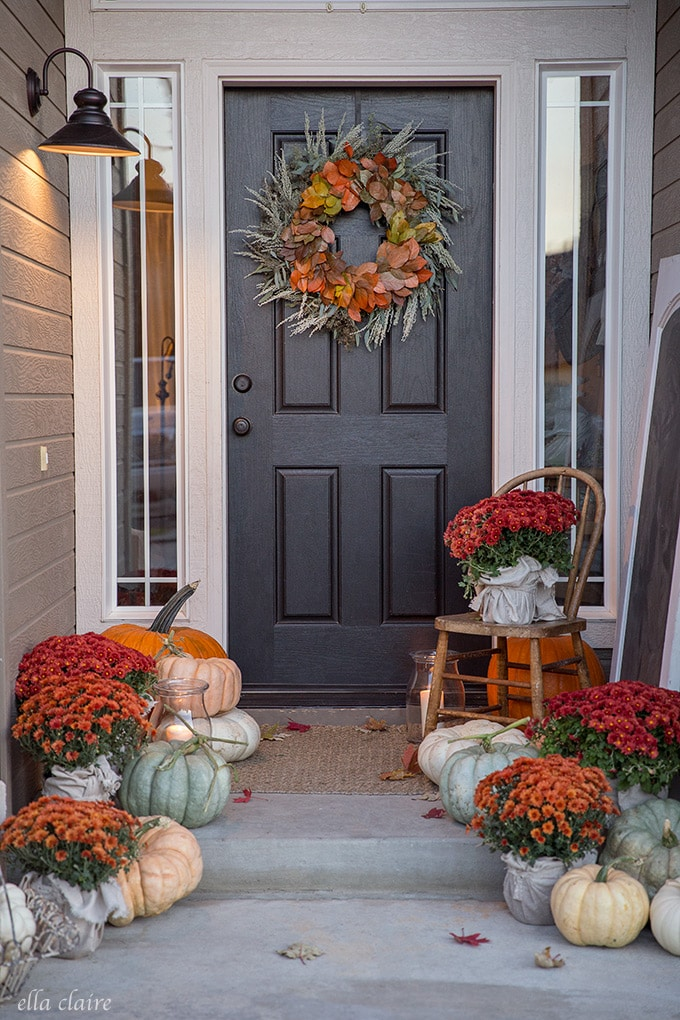 This cozy porch is dressed up for fall with traditional autumn colors- red and orange mums and muted green and white fairytale pumpkins.