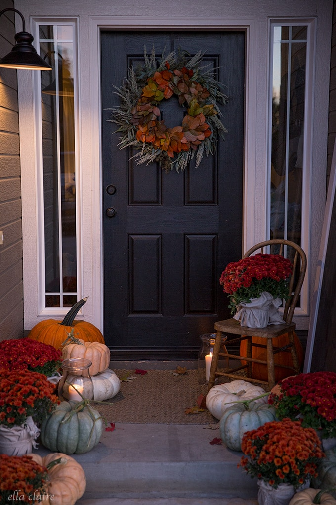 Cozy fall porch at dusk- decorated with mums, pumpkins and candlelight
