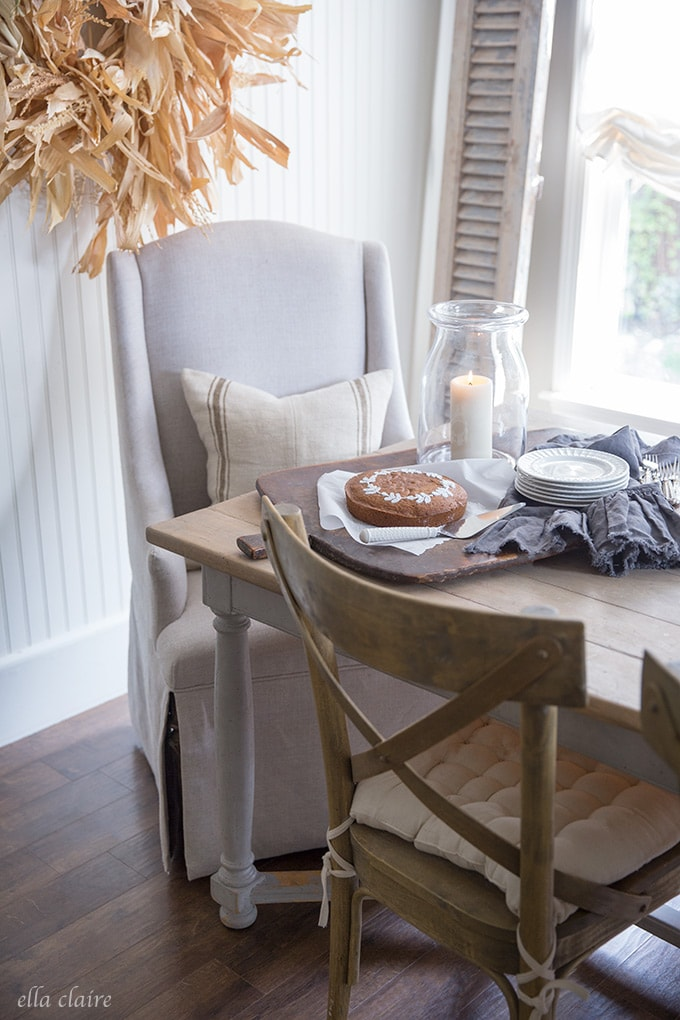 A cozy fall table with pumpkin cake candlelight, and a cozy pillow