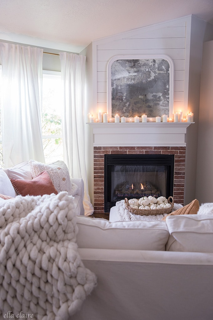 The warm glow of candlelight in a cozy fall family room- a halloween space with fun decorations