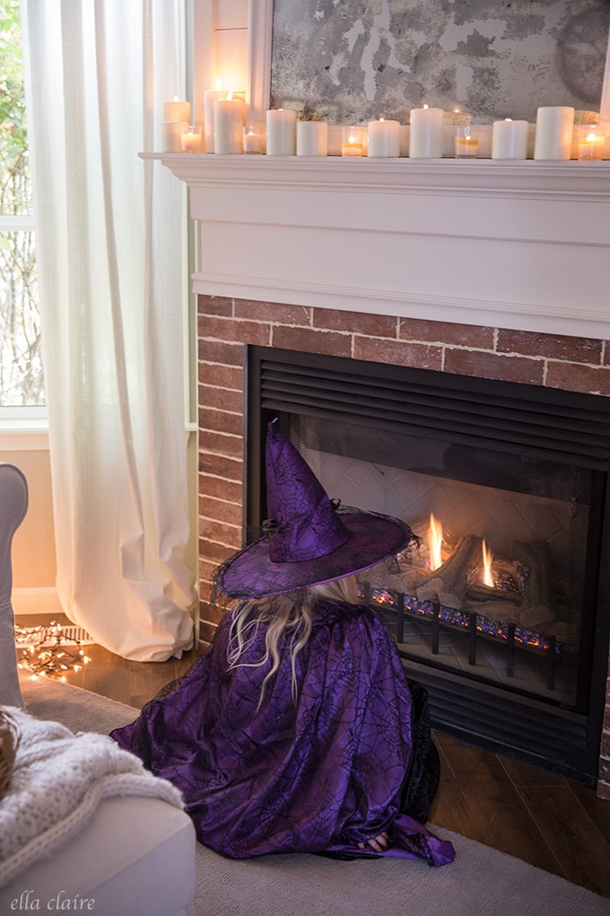Cute little witch warming by the fire