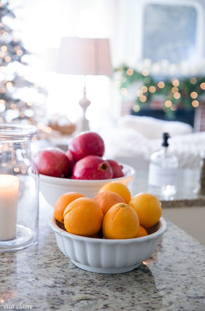 pomegranates and oranges in a Christmas kitchen with the glow of twinkle lights.