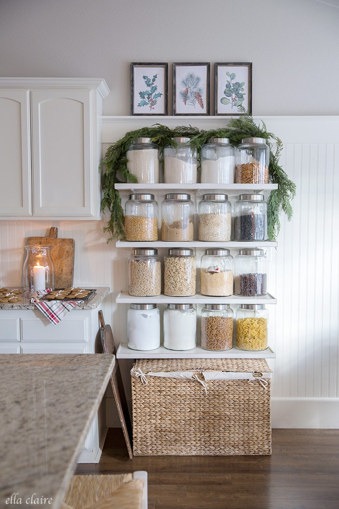 DIY jar shelves decorated for Christmas with a simple garland and vintage botanicals. A practical and beautiful way to add extra storage to a kitchen.