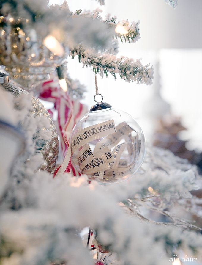 Sweet little sheet music paper strips in this clear glass ornament on a vintage inspired tree.