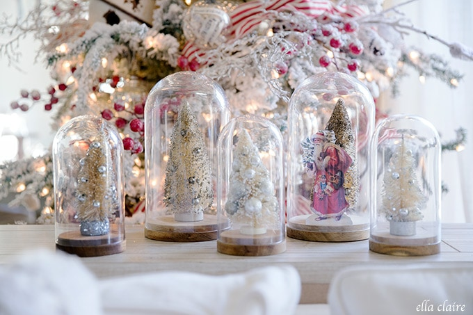 A little vintage santa and vintage bottle brush trees in cloches next to a nostalgic red and white Christmas tree.