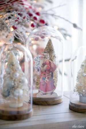 A little vintage santa and collected bottle brush trees in cloches next to a nostalgic red and white Christmas tree.