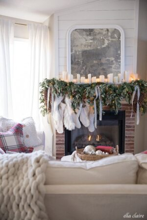 Collection of white stockings hung by a cozy fireplace draped in greens, red bells, and ribbons