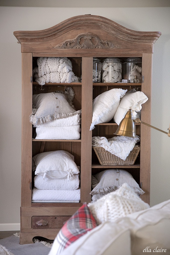 Cabinet with vintage linens, quilts and pillows in a vintage inspired Christmas living room