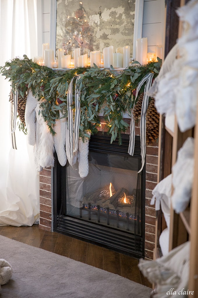 A cozy Christmas mantel with greens, candlelight, and cream stockings.
