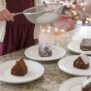 Homemade Gingerbread Cake dusted with powdered sugar, made in these adorable house molds are perfect for the Christmas season.