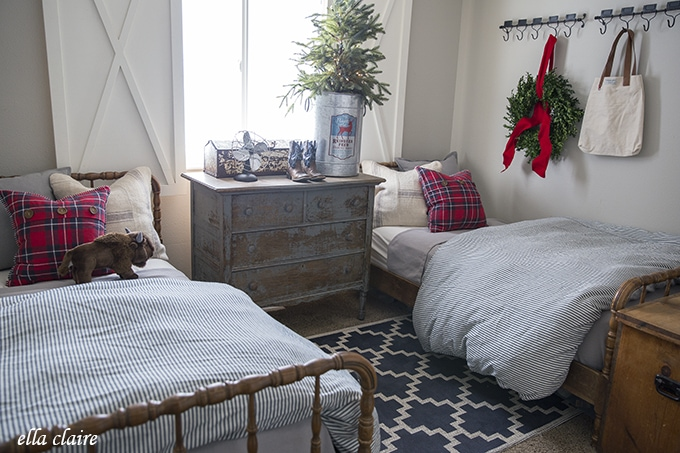 vintage beds in a farmhouse Christmas little boys room decorated for the holidays with red plaid, Navy blue and gray.
