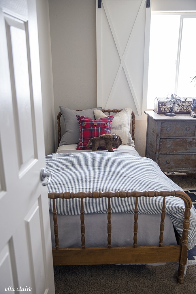 Plaid pillows and a favorite stuffed animal in a farmhouse Christmas little boys room