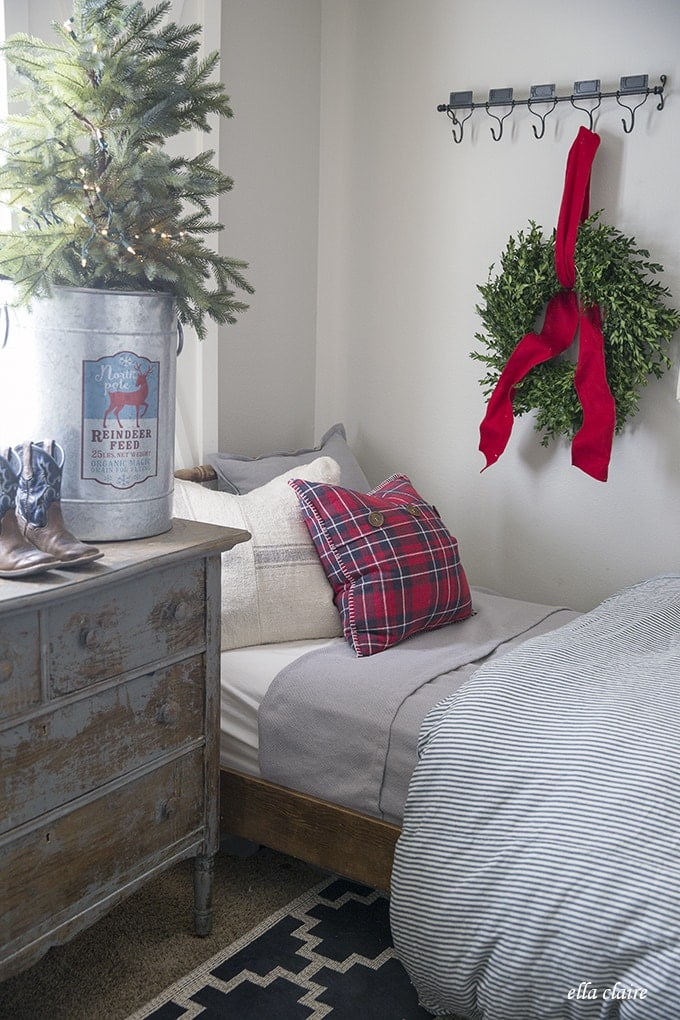 live boxwood wreath in a Christmas Farmhouse little boys room with red, blue, gray, plaid and a Christmas tree in a bucket