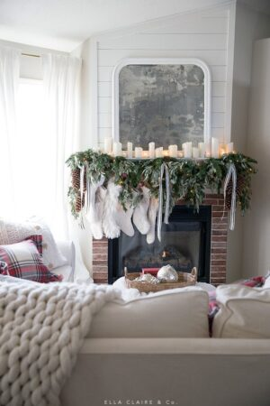 A Christmas mantel with greenery, cream stockings, twinkle lights, and the warm glow of candlelight. A Classic holiday mantel with traditional colors.