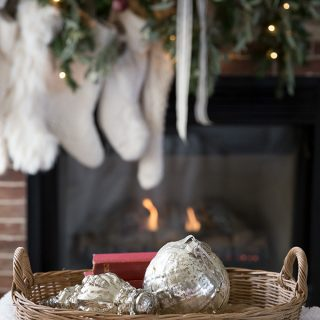 Simple mercury glass ornaments are a perfect holiday accent in front of a cozy fire and Christmas mantel.