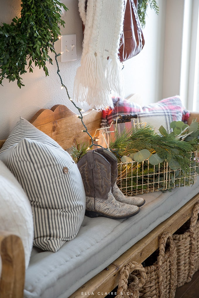 A cozy Christmas entryway with twinkle lights, classic reds and greens, and scarves.