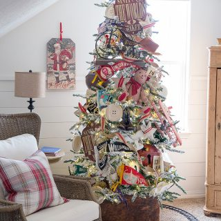 A flocked Christmas tree decorated with vintage toys, pennant banners, grain sack accents, and bells.