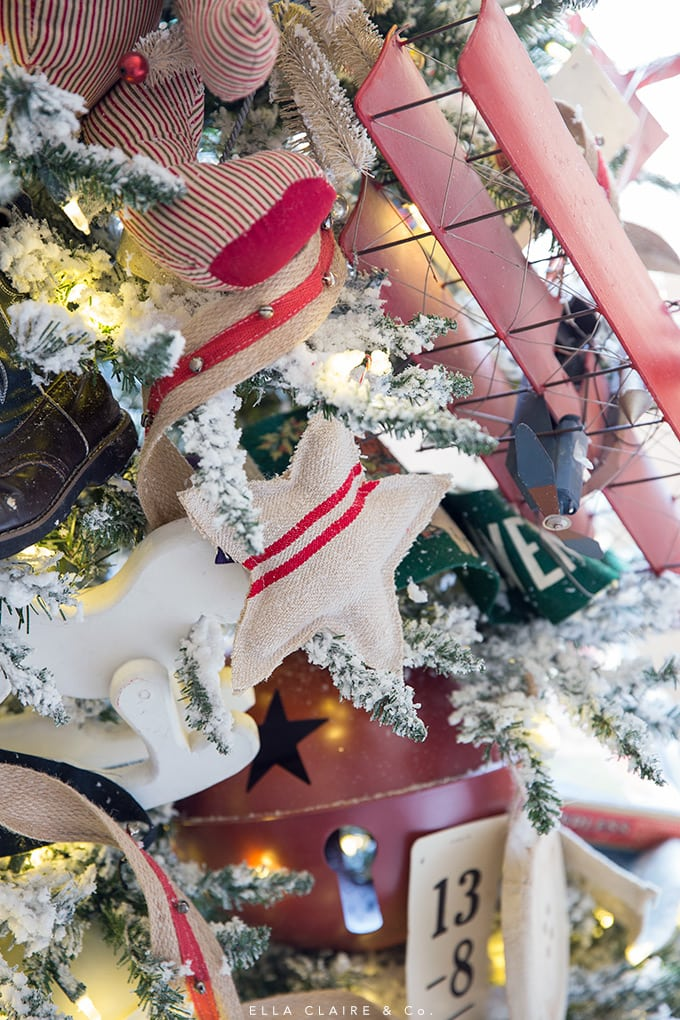 Grainsack stars, vintage toy airplane, and other vintage toys decorate this flocked Christmas tree.