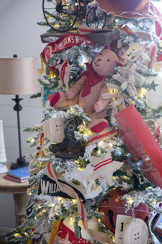 A flocked Christmas tree is decorated with vintage toys and pennants for nostalgic childhood theme.