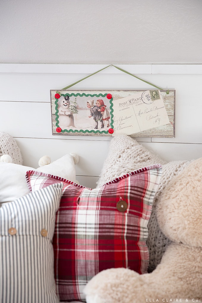 Vintage postcard art above an antique pine bed in a cozy playroom reading nook decorated for vintage farmhouse style Christmas