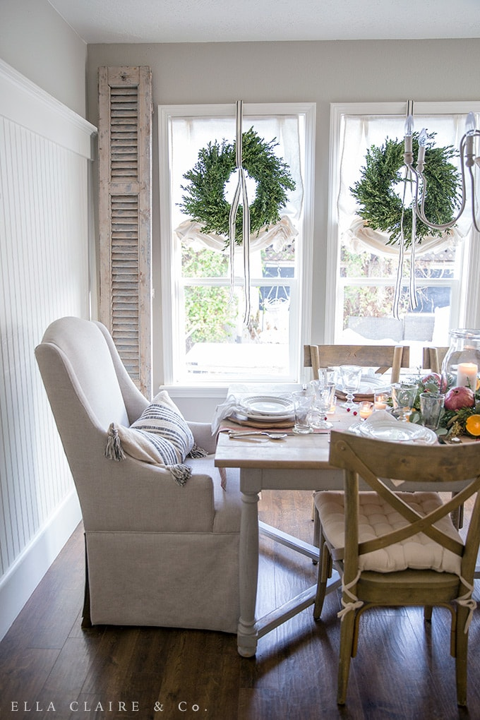 fresh Boxwood wreaths hung with ribbon in these dining room windows add Christmas charm to this farmhouse inspired space.
