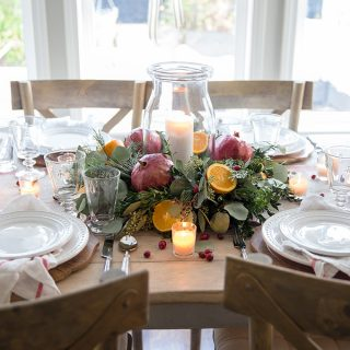 A simple DIY Christmas centerpiece with fresh greenery, oranges and pomegranates, and the soft glow of candlelight