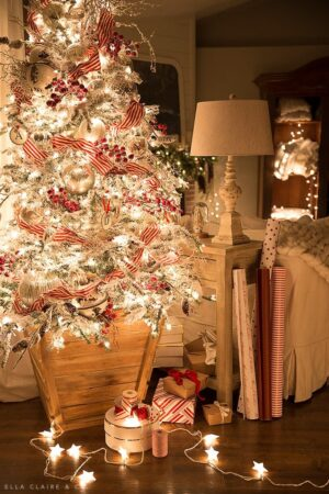 A flocked Christmas tree decorated with red and mercury glass (silver) accents, aglow in the quiet magic of a Christmas night.