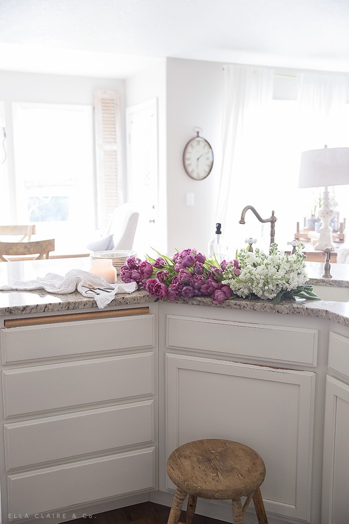 A sink full of fresh spring tulips and flowers- a pretty pop of color while decorating the french country house for the season.
