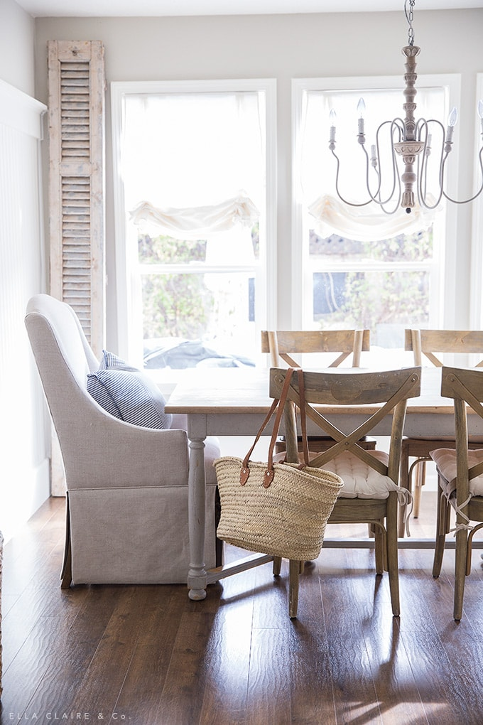French country decorating in a simple dining room with reclaimed shutters, a french market basket, and cozy seating.